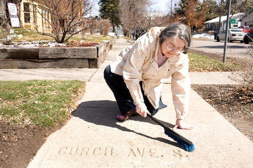 Kay McAllister sweeps off a sidewalk marker to reveal a mispelled Church Street on Friday. McAllister has documented much of Bozeman's century-old sidewalk markings and is in booklet form at the Pioneer Museum.