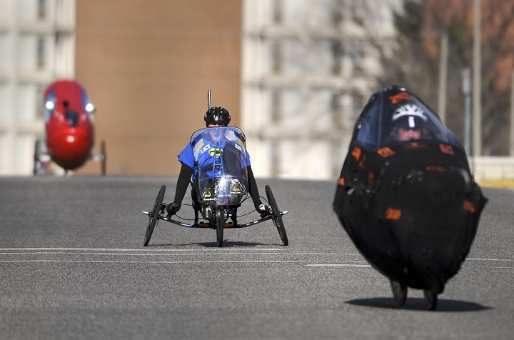 Cara Duberstein, a senior in mechanical engineering at Montana State University, center, peddles through campus Sunday morning during the ASME Human Powered Vehicle Challenge speed endurance event.